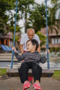 child being pushed in a swing by adult
